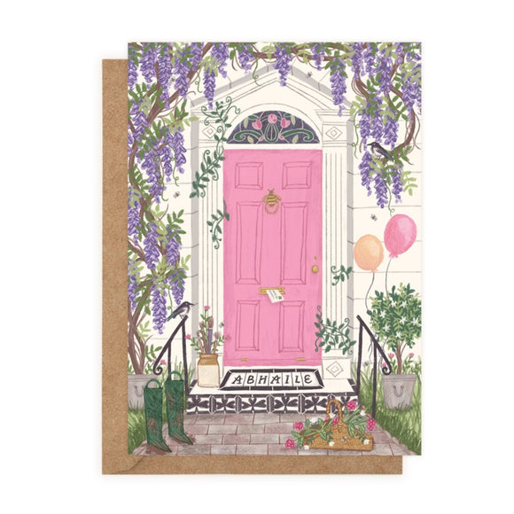 An illustration of a pink Georgian door with a doormat that says 'ABHAILE'. There are green wellies to the left and a pair of orange and pink balloons to the right. Purple flowers hang around the door from a tree.