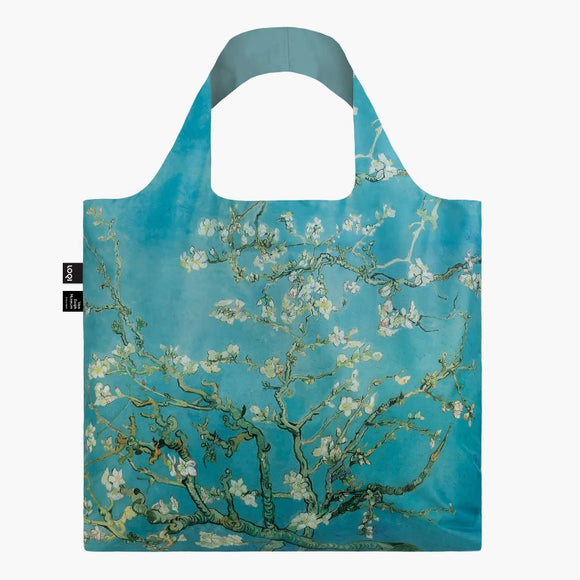 A square bag covered in a painting of green tree branches with white flowers, against a blue background. The handle lining is a matching blue.