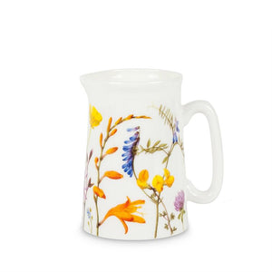 A small white jug covered in paintings of flowers in different types and sizes, in orange, yellow, blue, purple, and pink.