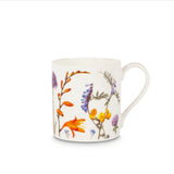 A white mug covered in paintings of flowers in different types and sizes, in purple, orange, pink and yellow.