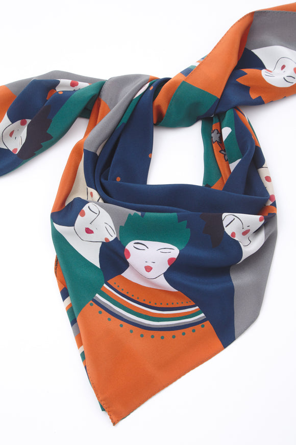 The scarf folded into a neckerchief showing a navy background with simple illustrations of women from the waist up in orange, green, white and grey.