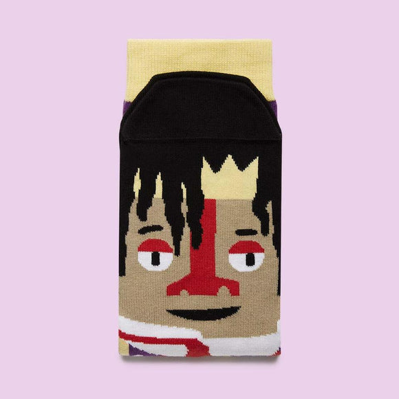 A folded sock with a cartoon illustration of a man with black dreadlocks and a white collar with red tie, on the foot part.
