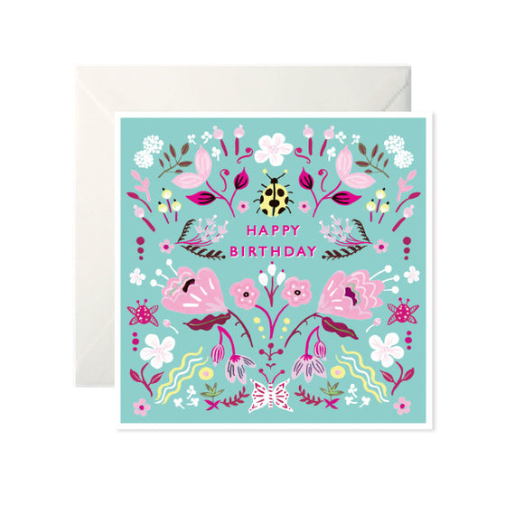 A turquoise card with drawings of flowers and insects in different shades of pink and some yellow. 'Happy Birthday' is written in pink capital letters with a yellow beetle above.
