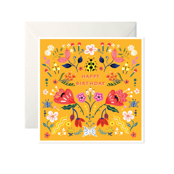 An orangey yellow card with colourful drawings of flowers and insects. 'Happy Birthday' is written in red capital letters with a yellow beetle above.