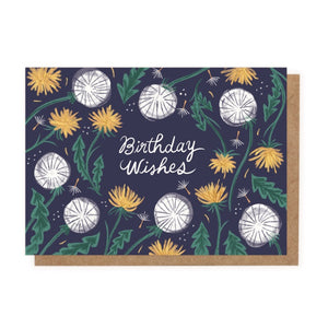 A navy card with 'Birthday Wishes' written in white cursive in the centre. It is surrounded by drawings of yellow and white dandelions.