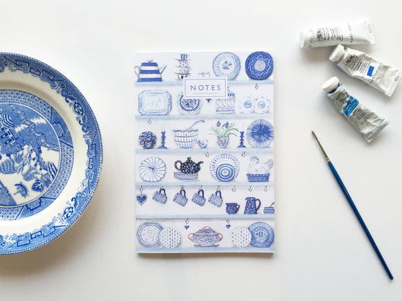 A white notebook with an illustration of shelves. They are neatly filled with a variety of dishes in shades in blue. 'Notes' is centred at the top on capital letters.