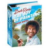 A book stands upright. On the cover is a man with curly hair, Bob Ross, holding a paintbrush and smiling, behind him is a painted landscape. The title is across the top in red and white. The title is also written along the spine.