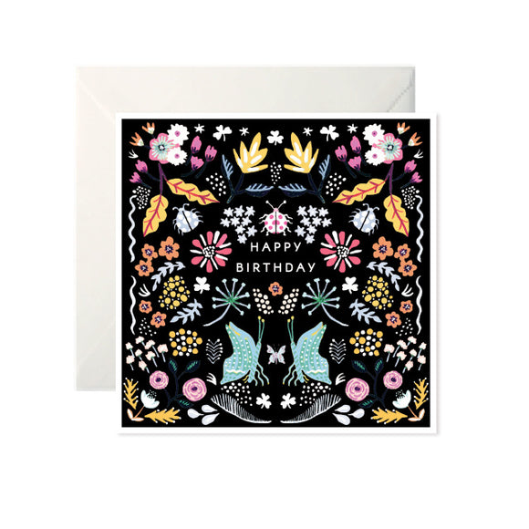 A black card with illustrations of flowers and leaves in white, orange, yellow and pink. In the centre is 'Happy Birthday' in white capital letters. Below is two butterflies in blue.