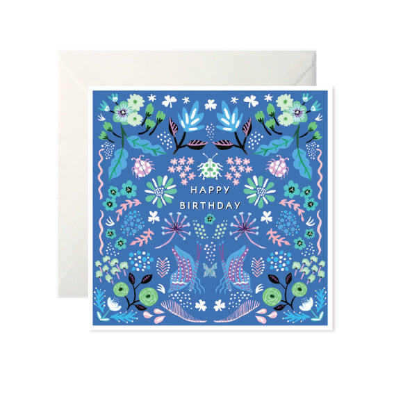 A dark blue card with illustrations of flowers and leaves in white, pink, green and different shades of blue. In the centre is 'Happy Birthday' in white capital letters. Below is two butterflies in blue and purple.