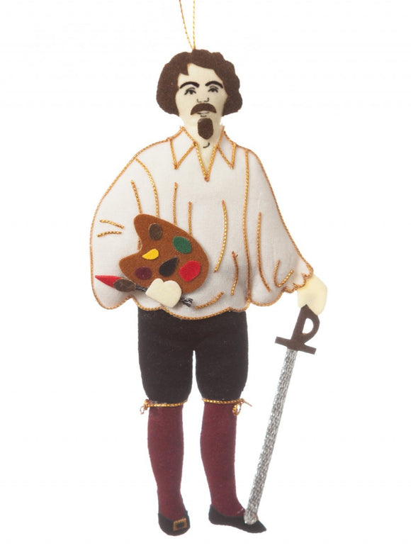 A felt man with a goatee, loose white shirt and wine knee high socks, detailed in gold thread, holding a silver sword and mini paint palette and brush, hanging from a golden thread.