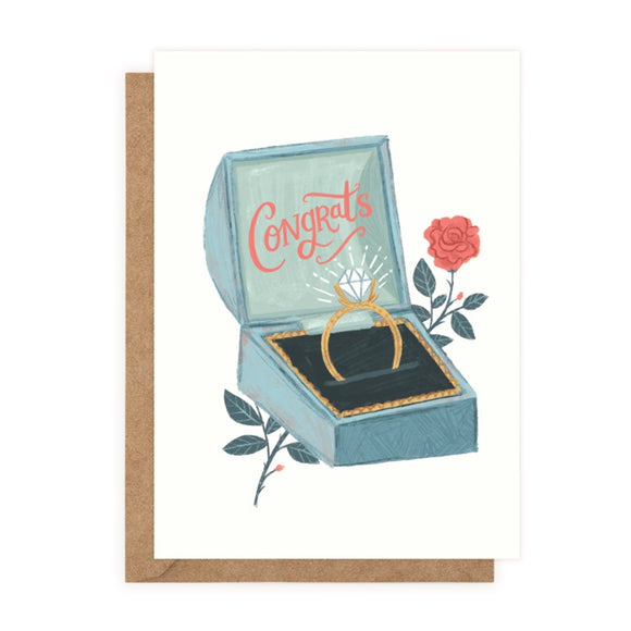 A white card with a drawing of an open blue ring box. Inside the lid 'Congrats' is written in red cursive. In the base is a gold diamond ring. A red rose is behind the box.