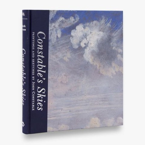 Most of the cover is a painting of a cloudy blue sky. The title is in silver letters vertically down the left side in a navy bar that wraps round onto the binding.