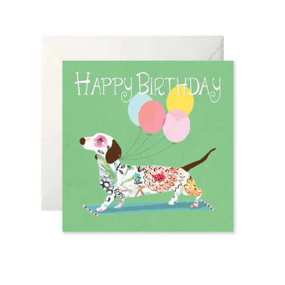 A green card with 'Happy Birthday' written in white across the top. Below is a white dog covered in a floral pattern with four balloons attached to it.