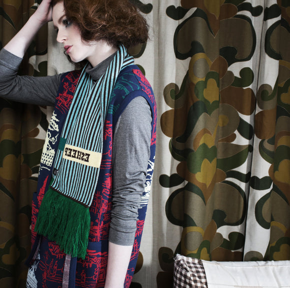 A model standing in front of retro curtains wears the scarf around her neck. The scarf has narrow dark brown and pale blue stripes, edged with thick green fringing. An horizontal stripe in pale yellow has in dark brown letters the word