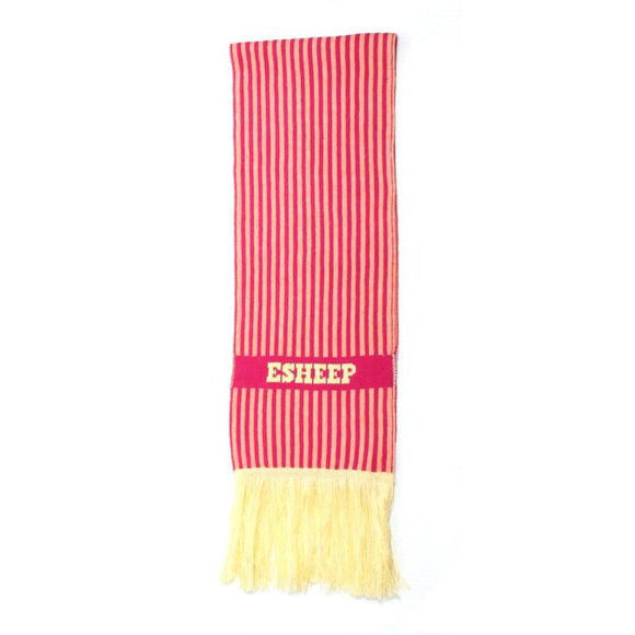 A narrow rectangular scarf shown folded in half. It has narrow pink and pale coral vertical stripes and pale yellow fringing at the end. An horizontal pink stripe features the word