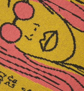 Detail from knitted triangle scarf. It shows the main figure of the design, a pink haired lady wearing pink sunglasses. The illustration outline is in black against the mustard background.