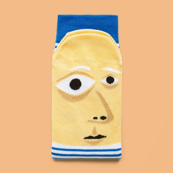 A folded sock with a cartoon illustration of a bald man with facial features in different sizes, on the foot part.