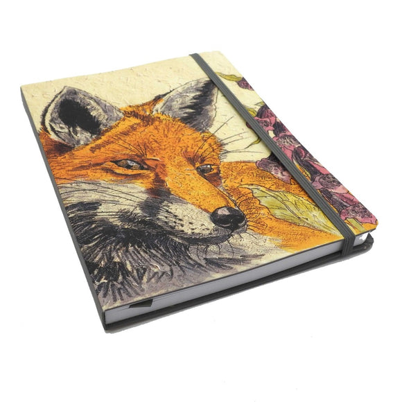 A notebook with a close up illustration of a foxes head taking up most of the cover. A purple foxglove flower goes up the right side. It is held closed by a dark grey elastic matching the grey spine.