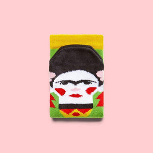 A folded sock with a cartoon illustration of a woman with black hair and joined eyebrows with red cheeks and lips on the foot part.