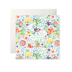 A white card with a colourful painted pattern of fruits and flowers. 'Lots of Love' is in the centre in mint capital letters.