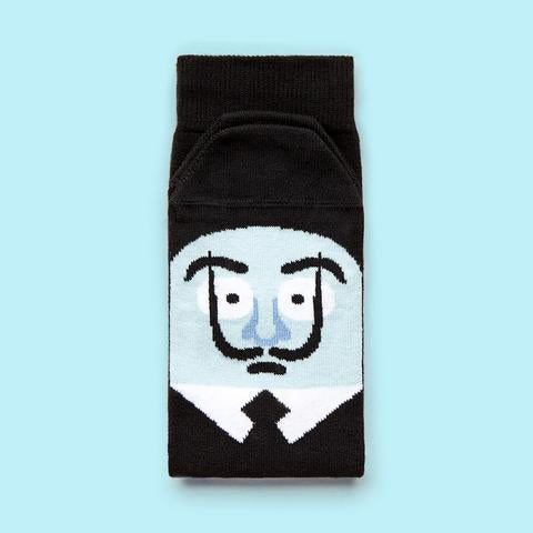 A folded sock with a cartoon illustration of a man with a blue face, black hair, a pointy black moustache, and black suit on the foot part.