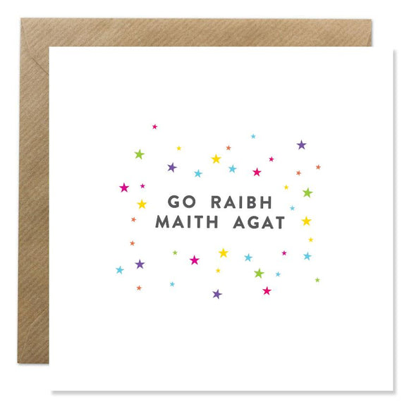A white card with 'Go raibh maith agat' written in the centre in black capitals. It is surrounded by small stars in different colours.