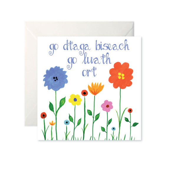 A white card with a simple, colourful drawing of flowers coming up from the ground. 'Go dTaga Biseach go Luath Ort' is written in blue cursive at the top.