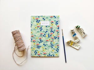 A green notebook cover with a colourful pattern of painted flowers in red, blue, white and yellow. 'Notes' is centred at the top in capital letters.