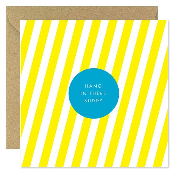 A bright yellow and white striped card with a blue circle in the centre. 'Hang in there buddy' is inside the circle in white thin capital letters.