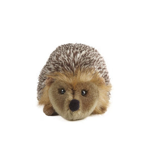 A soft, brown toy hedgehog. It's back is a mix of brown and white to look like spines. There are light brown tufts of hair around its head.