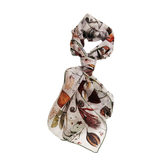 A rectangular white scarf knotted in a loop covered in illustrations of plants in shades of brown, green and yellow.