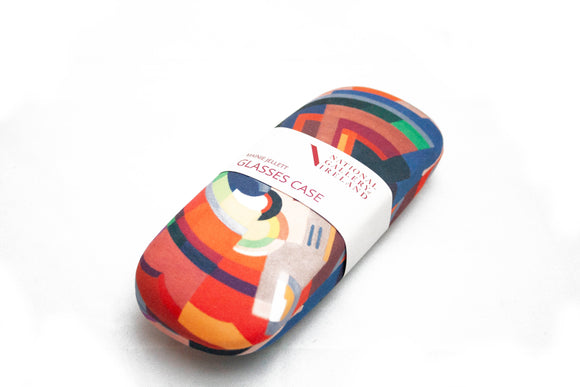 A glasses case of an abstract image of various shapes making a curved shape. It is primarily in shades of orange but with some blue and green as well. It has a label with its details across the middle.