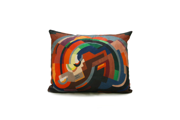 A rectangular cushion with an abstract image of various shapes making a curved shape. It is primarily in shades of orange but with some blue and green as well.