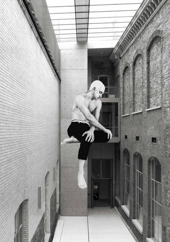 A black and white photo of a large, walled in courtyard between buildings with a glass roof. On the wall facing the viewer is an illustration of a shirtless man, legs crossed looking off to the side. It looks as if he is sitting on the wall.