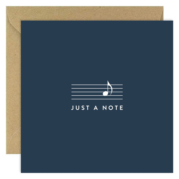 A navy card with lines from music paper in the centre with a single music note in white.'Just a note' is written underneath of white capital letters.
