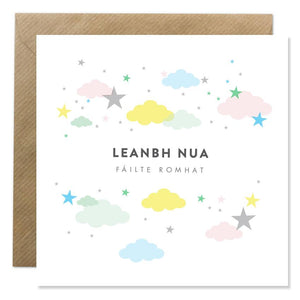 A white card with 'Leanbh Nua' in the centre and 'Fáilte romhat' underneath, both in black capital letters. Stars and clouds in pastel colours surround the text.