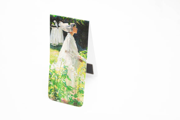 An open bookmark standing upright. The front is a woman in white walking through a garden with long stemmed white lilies in the foreground.