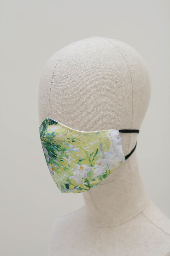 A shaped face mask on a mannequin head. The design is a painting of white flowers on a background of green made up of grass and leaves. It has black ear straps.