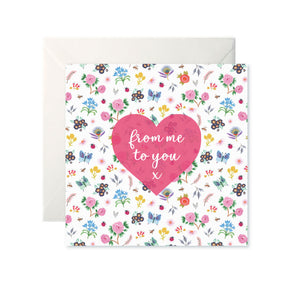 A white card with a pattern of colourful, small, simple flowers and butterflies. A pink heart is in the centre with 'from me to you x' in white cursive inside.