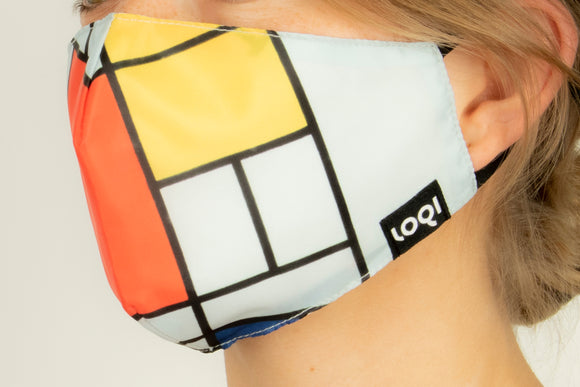A face mask on a person, shown from a side angle. The mask is made up of white, yellow, and red squares separated by black lines. It has the loqi logo on the edge and the ear straps are black.