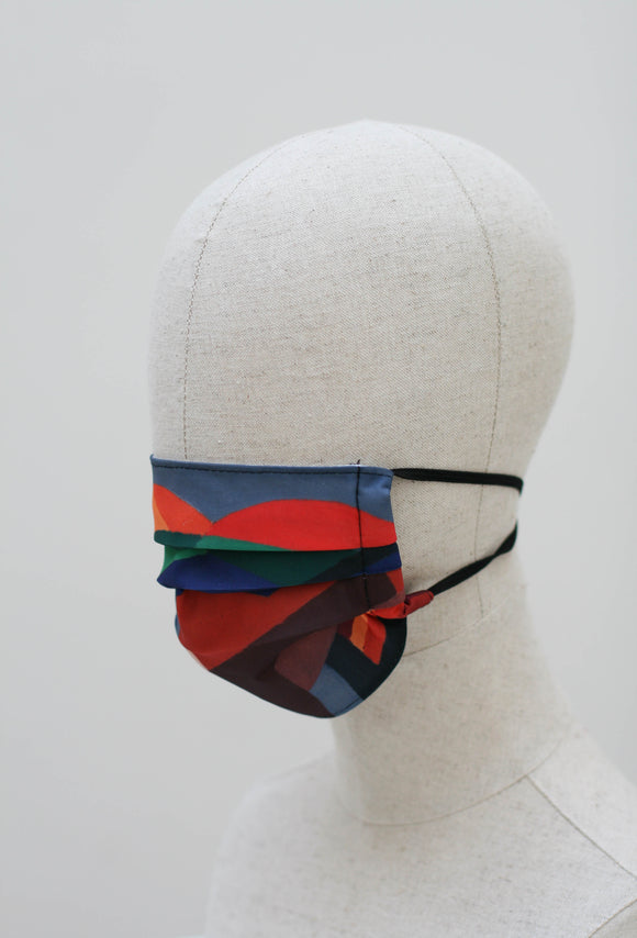 A pleated face mask is on a mannequin head. The design is a mix of abstract shapes in different colours. It has black ear straps.