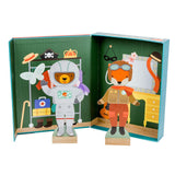 The box open looks like a dressing room with a rail of clothes printed on the left and a dressing table on the right. The bear stands separate dressed as an astronaut and the fox as an old fashioned pilot.