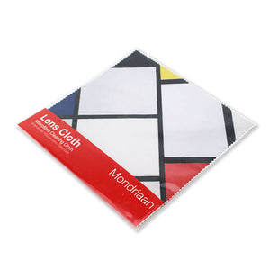 A lens cloth in a clear plastic package with a red label. The cloth is made up of white squares and rectangles separated by black lines. There is yellow, red, black and blue parts of squares at the edges.