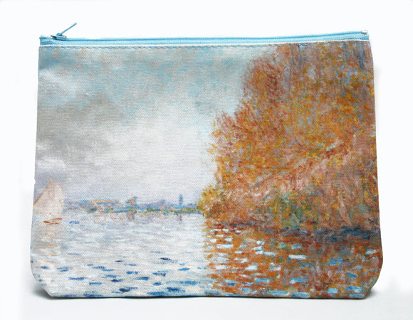 A zip top bag with an impressionist painting of a light blue sky and matching coloured lake. The right of the image is dominated by a large tree in autumn oranges which reflects into the water. On the left is a small boat with its white sail open.