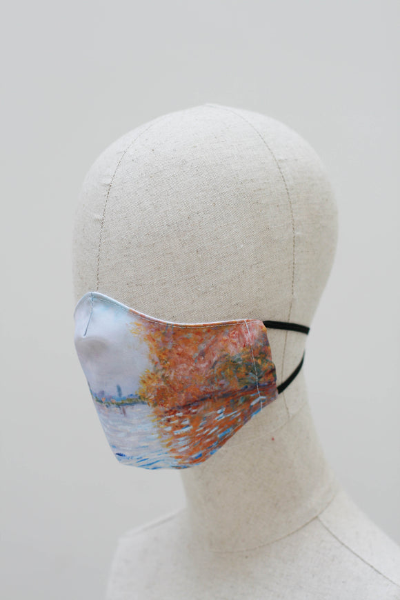 A shaped face mask on a mannequin head from a side angle. The design is an impressionist style painting of an orange autumn tree reflected into a light blue lake, with a matching light blue sky. The lake and sky continue around the mask. It has black ear straps.