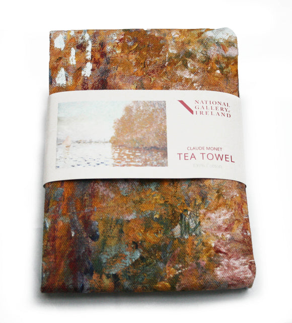A folded tea towel with a grey label around the centre. The label shows aan impressionist painting of a light blue sky and matching coloured lake. The right of the image is dominated by a large tree in autumn oranges which reflects into the water. On the left is a small boat with its white sail open.
