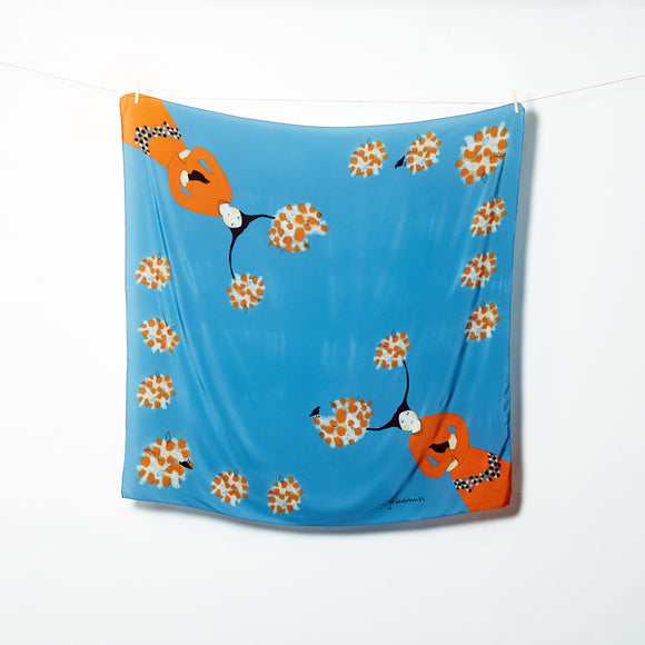 A bright blue scarf laid flat. In two opposite corners is a stylised illustration of a woman wearing an orange dress and holding a black bird. Her black hair is split into two branches with white and orange puff on the ends. These circular puffs are repeated along the other corners of the scarf.