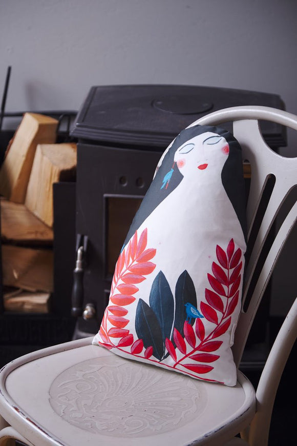 A roughly oval shaped flat cushion with a squared off bottom. It is printed with a simple, stylised design of a nude woman with long black hair. Growing up from the bottom are big navy leaves and two tall red plants covered in smaller leaves, with a light blue bird sitting on one.