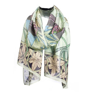 A scarf in pale green draped around an invisible neck. There are pale peach lilies at the bottom edge of the scarf.