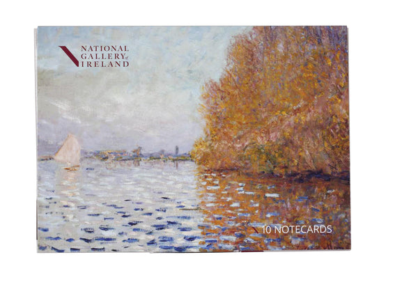 A box with an impressionist painting of a light blue sky and matching coloured lake. The right of the image is dominated by a large tree in autumn oranges which reflects into the water. On the left is a small boat with its white sail open.